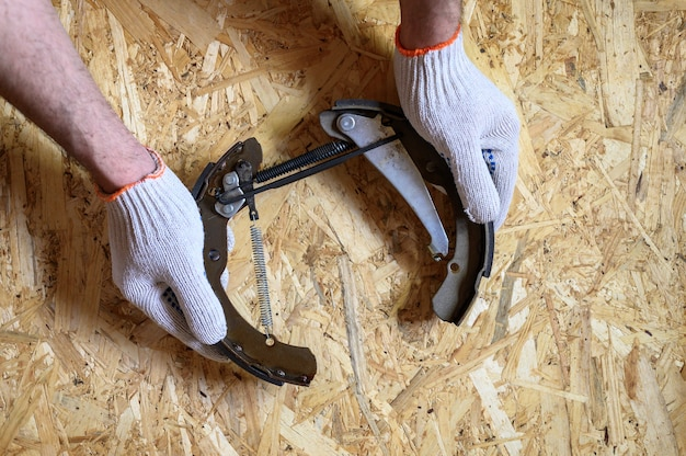 Men's hands in gloved are holds car drum brake disassembled on a sheet of osb plywood background. flat lay, top view