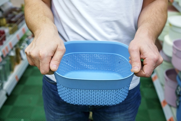 男性の手はプラスチックの箱のバスケットを保持します