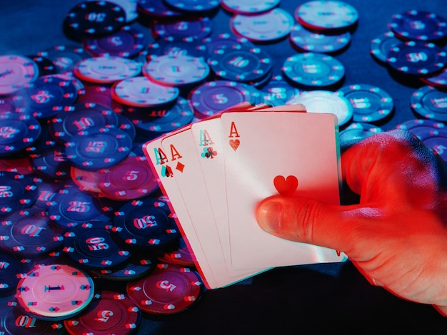 Men's hands hold aces cards against the background of playing chips. the photo shows smoke. 3d glitch virtual reality effect