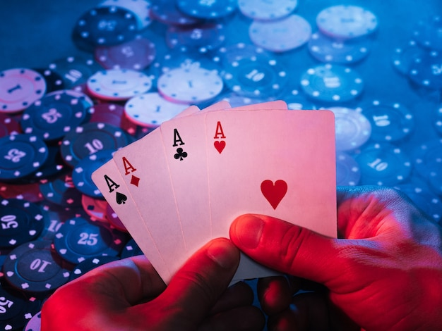 Men's hands hold aces cards against the background of playing chips. the photo shows smoke