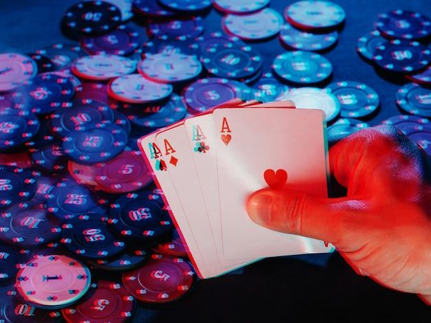 남자의 손은 칩 게임의 배경에 대해 에이스 카드를 보유합니다. 사진은 연기를 보여줍니다. 3d 글리치 가상 현실 효과