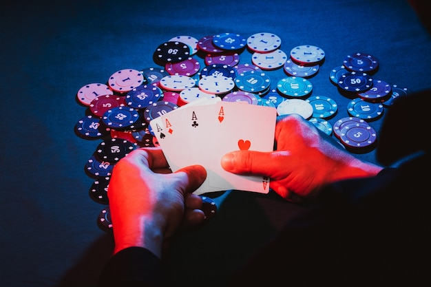 Men's hands hold cards , a set of aces over playing chips