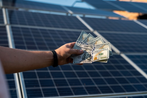 Men's hands hold dollars as a profit from the production of alternative energy. solar panels