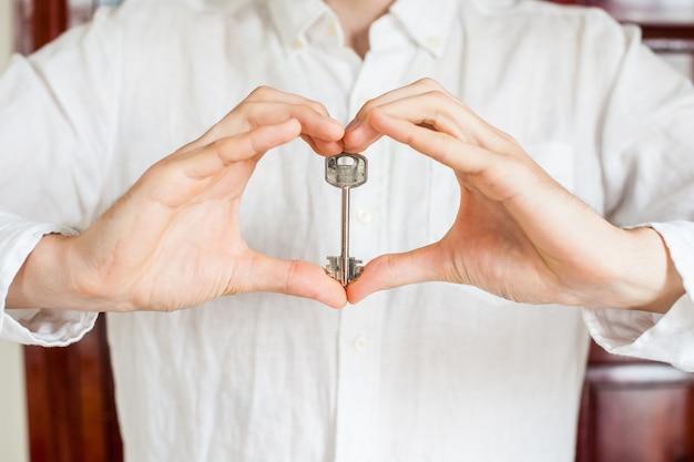 男性の手は、木製のドアの背景にハートの形で家の鍵を保持しています。不動産コンセプトを所有