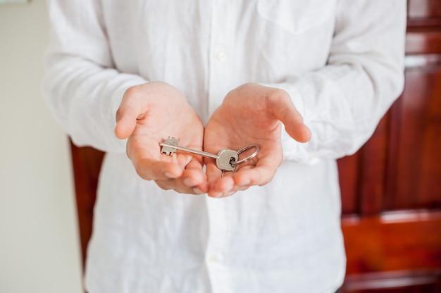 男性の手は木製のドアの背景に家の鍵を保持します。不動産コンセプトを所有