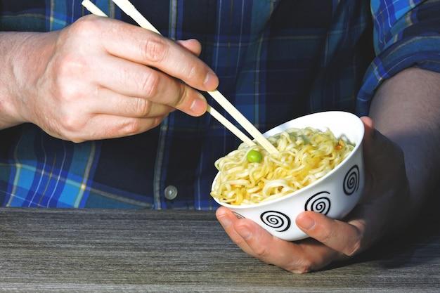 Men's hands hold noodles with chopsticks. chinese noodles, sticks, hands.