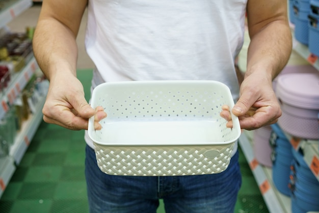 Le mani degli uomini tengono un cestino della scatola di plastica