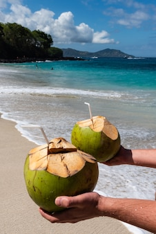 Men's hands hold two fresh coconut cocktails on the beautiful beach at sunny day.