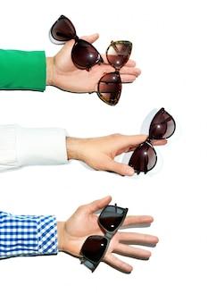 白い背景の上にサングラスを保持している男性の手。スタジオ撮影。