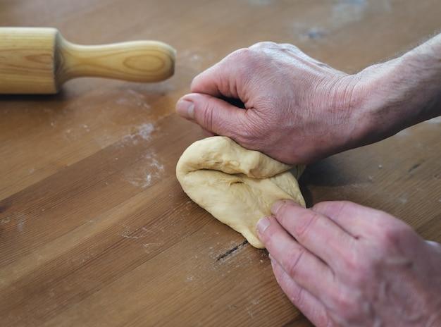 男性の手が木製のテーブルにパンを混練します。ベーカリーのコンセプトです。