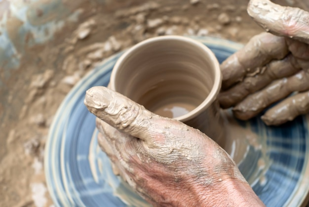 Men's hands making a clay mug on a potter's wheel