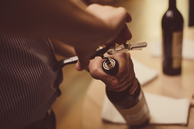 Men's hands open a bottle of wine with a corkscrew