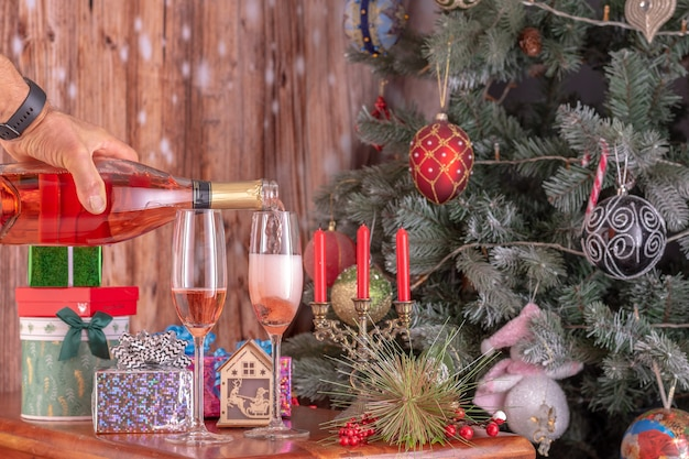 Men's hands pouring champagne from a bottle into champagne flutts against the background of a new year tree and presents.