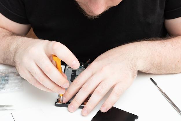 남자의 손은 휴대 전화를 수리하고 드라이버로 나사를 조입니다.