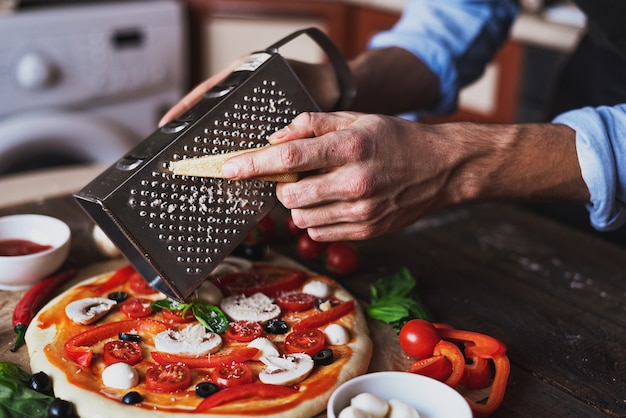 Men's hands tinder parmesan for unprepared pizza with mushrooms, olives and cherry tomatoes