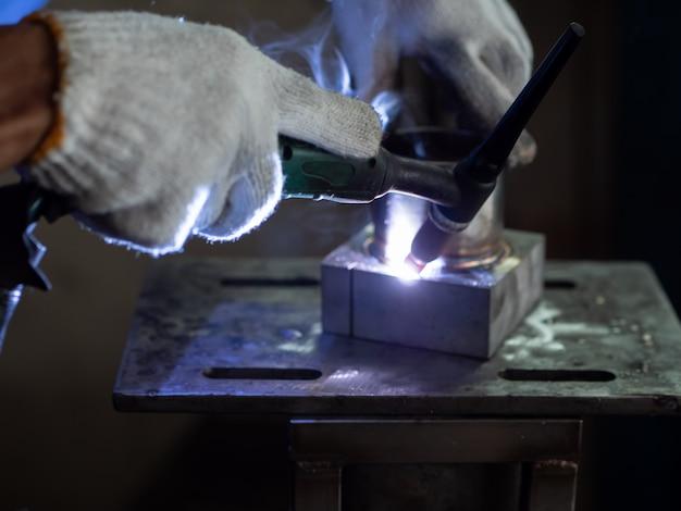 Men's hands with argon welding machine.
