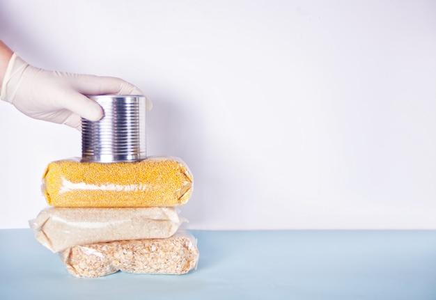 ゴム手袋をはめた男性の手は、食べ物と一緒に缶を与えます。食料の寄付。流行時の食品の配達。非接触型製品の配送。