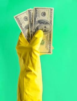 クリーニング用の黄色のゴム手袋をはめた男性の手は、青色の背景に100ドル札を保持します