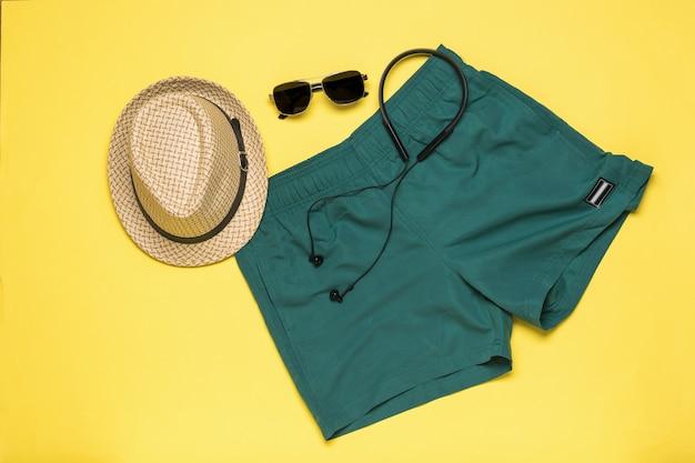 黄色い表面に男性用の帽子、ショートパンツ、メガネ、ヘッドフォン。夏の人気メンズアクセサリー。
