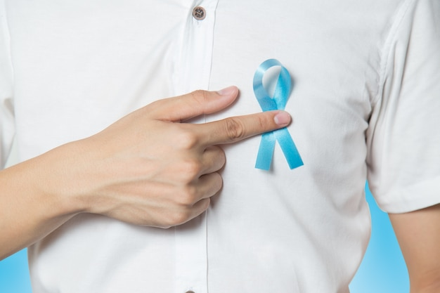 Men's healthcare concept - close up of male hand pointing to light blue ribbon for prostat