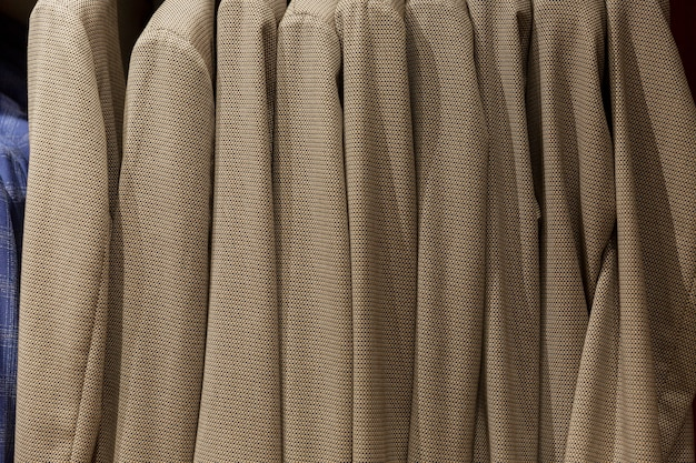 Men's jackets on hangers in the store. side view.