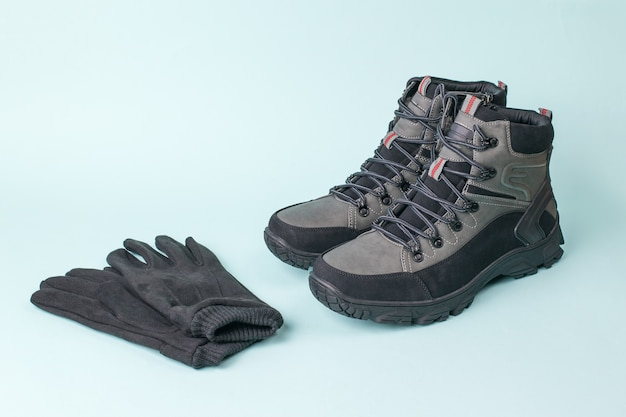 Men's leather gloves and boots on a blue background. men's shoes for cold weather. casual sports men's shoes.