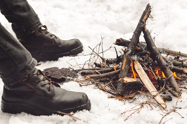 Men's legs in black hiking boots near a burning bonfire.
