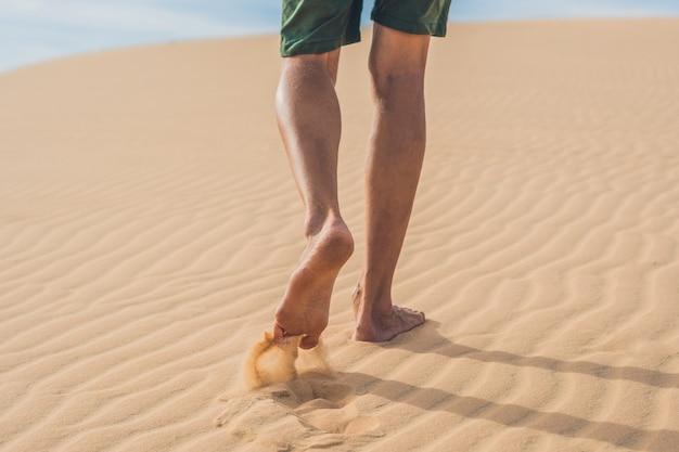 男性の足はベトナムの砂漠、ムイネーに行きます