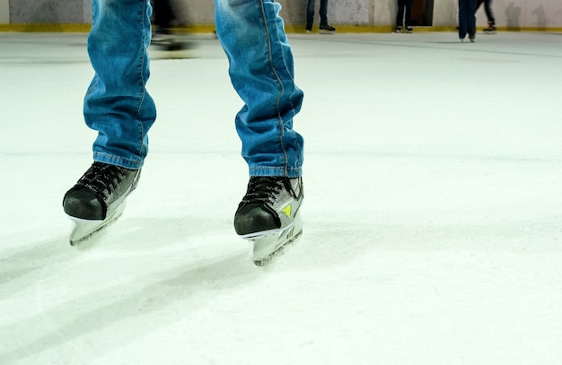 Men`s legs in ice skates and jeans