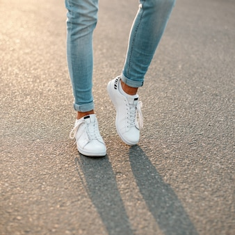 아스팔트에 흰색 유행 운동화에 파란색 세련된 청바지에 남자 다리. 확대.