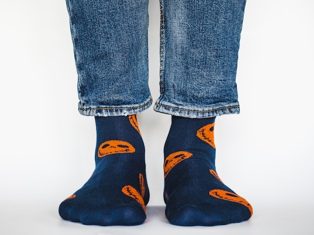 Мужские ноги, модная обувь, синие джинсы и пестрые длинные носки на белом изолированном фоне. крупный план. концепция стиля и элегантности