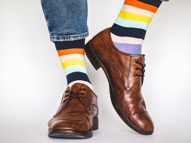 Men's legs, trendy shoes, blue jeans and variegated, long socks on a white,