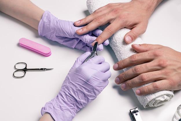 男性用マニキュア。ゴム手袋の美容師が男性の手でキューティクルをカット