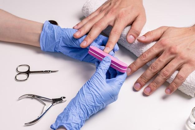 男性用マニキュア。ゴム手袋の美容師は、男性の手に爪を打ちます。