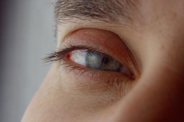 Мужские прищуренные глаза. прямой уставший взгляд в кадре крупным планом. Premium Фотографии