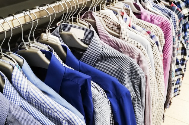 Men's shirts of different colors on hangers.