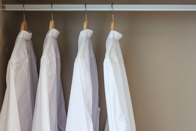 Men's shirts on hangers in wardrobe, closed up with copy space and text.