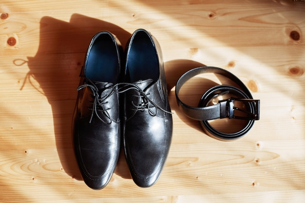 Men's shoes and belt on the floor.