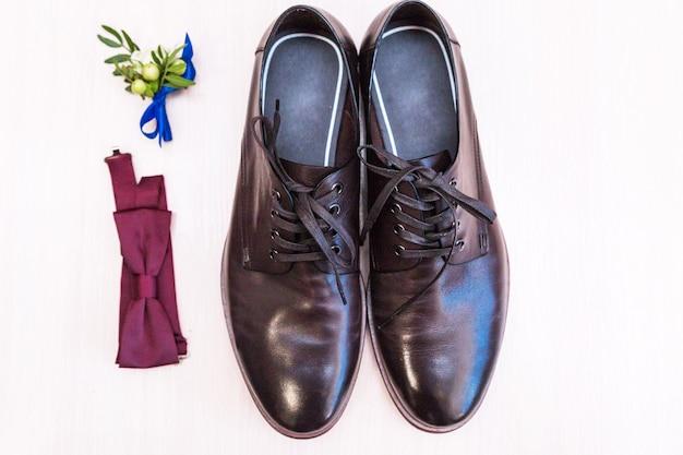 Мужская обувь, бутоньерка бабочки и жениха