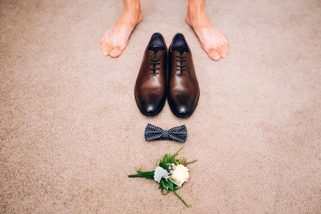 Мужские туфли из коричневой кожи. свадебная концепция мужская обувь, галстук-бабочка и бутоньерка, вид сверху.