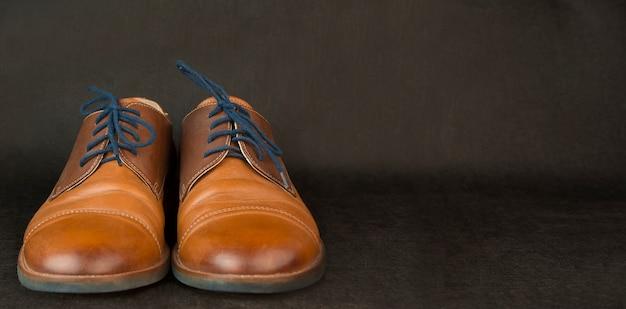 Мужская обувь на темном столе, концепция семьи. мужская классическая обувь. современная классическая обувь. баннер копирование пространства.