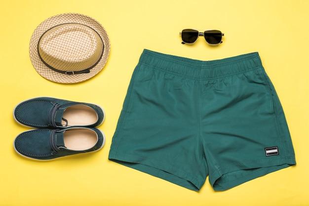 黄色の背景にメンズシューズ、ショートパンツ、帽子、メガネ。夏の人気メンズアクセサリー。