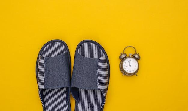 노란색 배경에 남성용 수면실 슬리퍼와 알람 시계. 수면 시간.