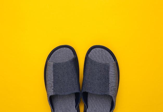 黄色の背景に男性用スリーピングルームスリッパ。