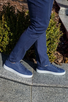 Men's sneakers or shoes made of genuine leather on men's legs close-up.