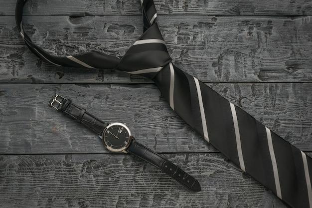 黒の背景にメンズストライプネクタイとクラシックな時計。フラットレイ。