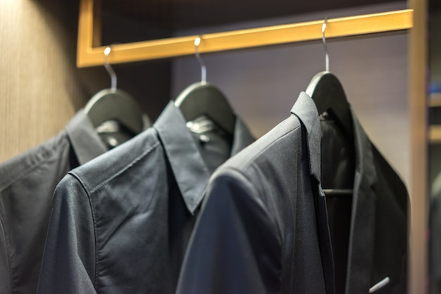 Men's suit jackets hanging on rail in a wardrobe, interior design. interiors.
