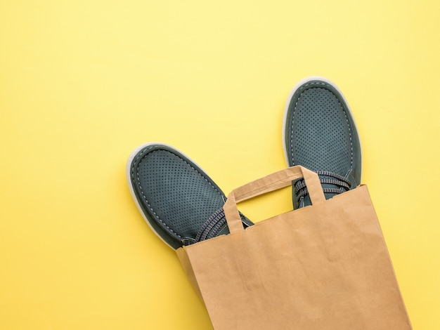 黄色の背景に紙袋の男性の夏の靴。靴を買う。フラットレイ。