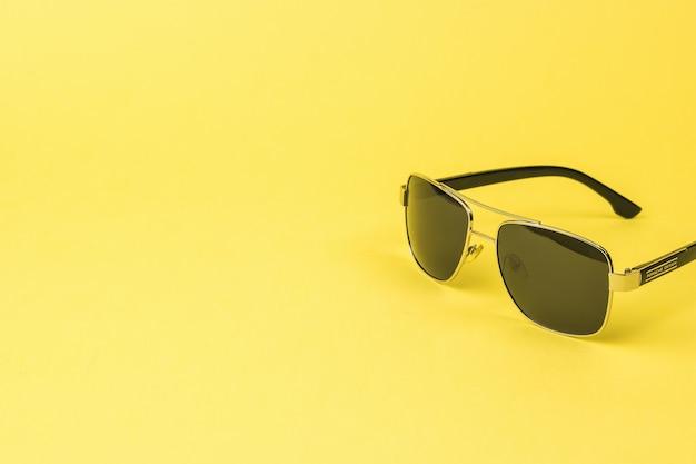 黄色の背景に日焼け止め用のメンズサングラス。ファッショナブルなメンズアクセサリー。