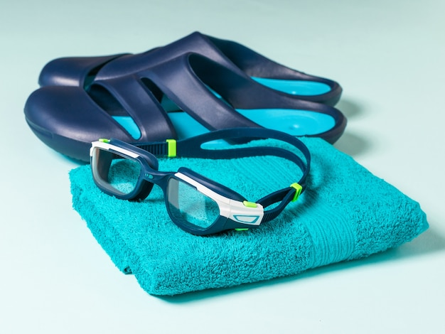 Men's swimming goggles on a towel and blue slates. accessories for swimming in the pool.